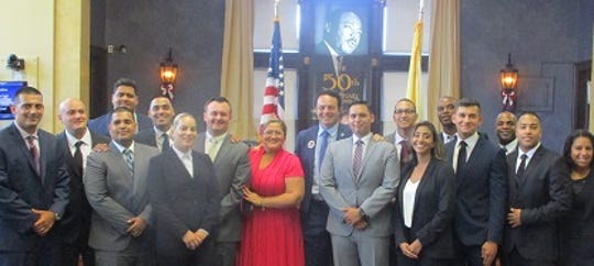 Paterson's 16 new police recruits with Mayor Andre Sayegh (blue suit in center) and City Council President Maritza Davila (red dress).