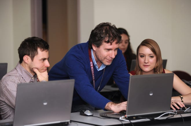 NMSU College of Arts and Sciences Dean Enrico Pontelli and students work together in a computer lab.