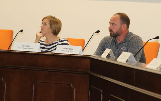Hayley Klein (left) and Chance Chase listen to a July 11 presentation during the Eddy County Energy Advisory Board meeting.
