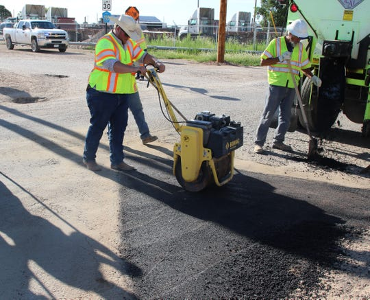 Eddy County Public Works Director Jason Burns smooths freshly poured pavement July 10.