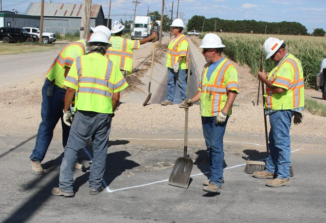 Members of an Eddy County road crew get ready to fill in a pothole July 10 near Otis.