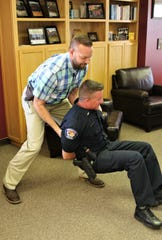 Sgt. Mark Gaines, left, of the Farmington Police Department finishes a demonstration of a head tilt takedown technique on Lt. Guy Postlewait.