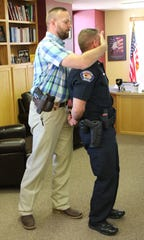 Sgt. Mark Gaines, left, of the Farmington Police Department demonstrates a head tilt takedown technique on Lt. Guy Postlewait.