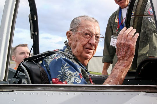 Navy veteran Frank Emond, 101, a Pearl Harbor survivor, waves after getting situated in a T-34 Mentor at the Pensacola Aviation Center on Friday before the start of his Veterans Flight to Pensacola Beach.