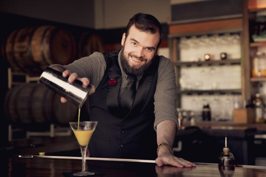 Bar manager Christopher Landry mixes up cocktails at the bar.