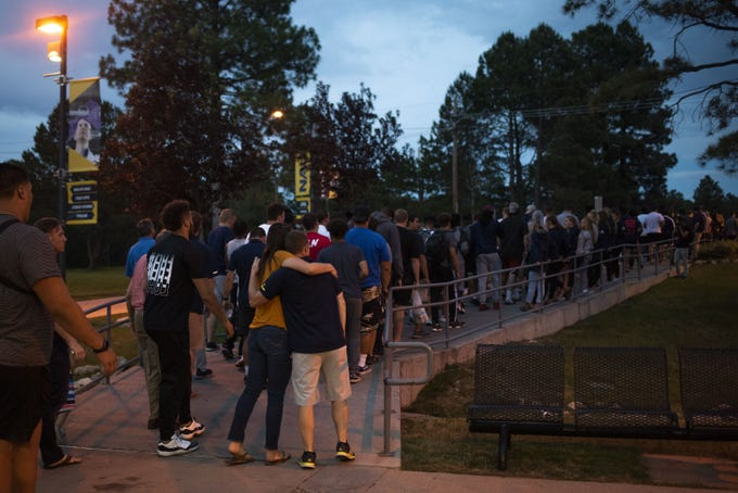 Mourners gathered at the Walkup Skydome parking lot on the Northern University University campus in Flagstaff, Ariz, July 12, 2019. A candlelight vigil was held on Thursday night to memorialize Malik Noshi, a NAU offensive lineman, who died suddenly on Sunday.