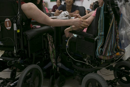 Residents of Hacienda HealthCare sit with their care providers inside the facility in Phoenix, Ariz. on July 9, 2019.