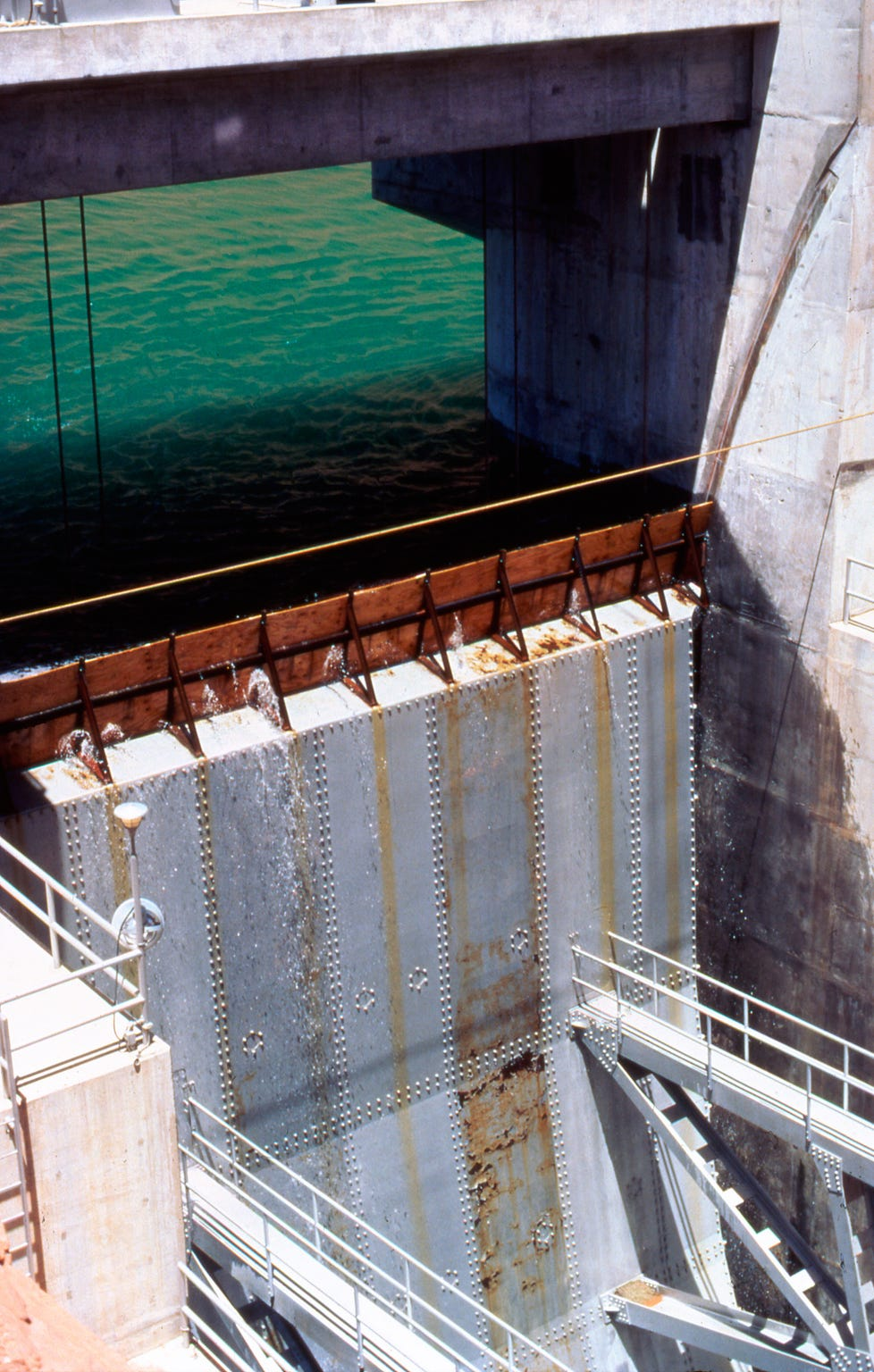 Lake Powell water levels rose steadily during June and July 1983, forcing the Bureau of Reclamation to use plywood barriers to keep the lake from spilling over the closed gates on Glen Canyon Dam.