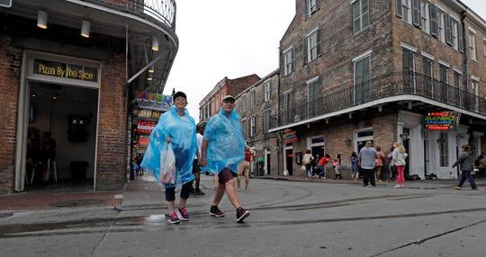 Una pareja de adultos caminan por el centro de Nueva Orleáns usando unos ponchos para la lluvia.