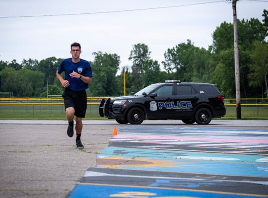 Aaron Smith runs across the parking lot at Port Huron Northern during a practice fitness test Friday, July 12, 2019, as part of the Port Huron Police Department's youth academy.