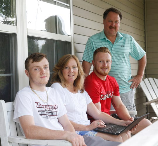 From left, Kyle, Cindy, Ryan, and Jim Wilson at their home in LaGrangeville on July 12, 2019. The family look at photos of Ryan's bicycle trip to Miami. Ryan raised money for ALS research in honor of his aunt.