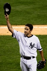 Mike Mussina  of the New York Yankees waves to the crowd after being taken out of the game in the seventh inning against the Chicago White Sox on September 18, 2008 at Yankee Stadium in the Bronx.