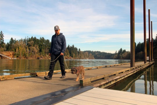 A man walks a dog on the dock at Champoeg State Heritage Area. The dock is closing for bank repair.