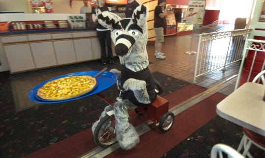 Wilbur, aboard his tricycle, peddles into the dining room at Gigglebees on a July afternoon in 2008 to deliver another pizza. Gigglebees closed in 2008.