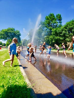 Children play in the water during Sioux Falls' first Hydrant Block Party at Bakker Park on July 11, 2019.
