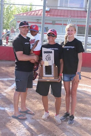 New Desert Hills softball coach Heidi Taylor (center) poses with the UHSAA 3A State Championship trophy, her husband, Wes, and her two children Hallee (right) and Camden (held by Wes).