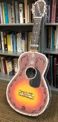 "Dave Gussack new edition of ""Art and Art Therapy"" features art created by inmates, including this guitar made with cardboard and ""inset"" with ""carved"" tendrils, the bridge is made of candy wrappers."