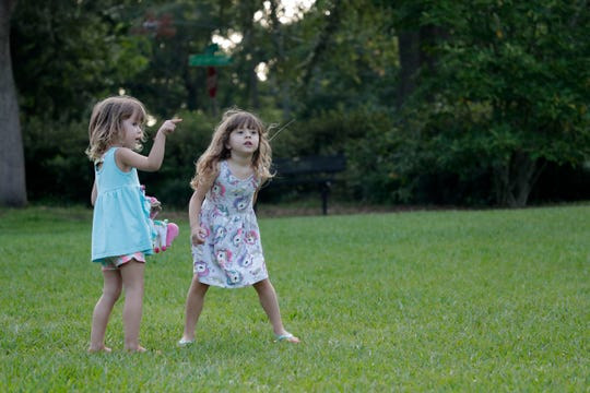 Twin sisters Irene, left, and Vivan, 3, play together at a park in Betton Hills Thursday, July 11, 2019.