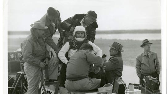 "Lt. Col. John Paul Stapp is strapped into ""Sonic Wind No. 1"", one of the rocket sleds used by Lt. Col. Stapp for physiological testing. Note the motion picture cameras at the forward edge of the sled platform to photograph Lt. Col. Stapp during the tests."