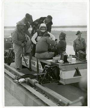 """Lt. Col. John Paul Stapp is strapped into """"Sonic Wind No. 1"""", one of the rocket sleds used by Lt. Col. Stapp for physiological testing. Note the motion picture cameras at the forward edge of the sled platform to photograph Lt. Col. Stapp during the tests."""