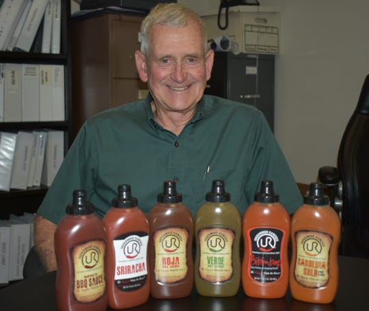 Craig Underwood displays the Sriracha sauce and five other sauces his company is making. Underwood Ranches won a $23.3 million award from a jury this month in a lawsuit involving longtime partner and Sriracha maker, Huy Fong Foods.