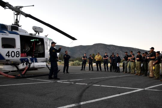 Helicopter crews participate in a safety briefing at the start of a nighttime training exercise in Lockwood Valley on July 11, 2019. They practiced dropping water on firefighting targets in the dark of night.