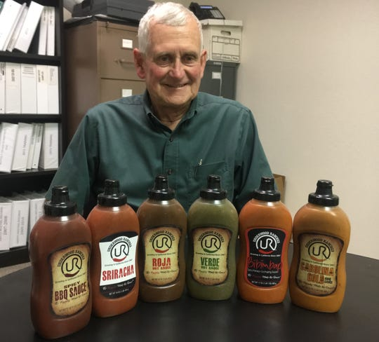 Craig Underwood displays the Sriracha sauce and five other sauces his company is making. Underwood Ranches won a $23.3 million award from a jury this month in a lawsuit involving longtime partner and Sriracha maker Huy Fong Foods.