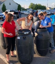 (From left) Vicki Vagnarelli and her daughter, Alicia, prepare a rain barrel to help conserve water during a rain barrel workshop sponsored by Upper Deerfield Township Environmental Commission and the American Littoral Society; as Zach Nickerson of the American Littoral Society also works on a rain barrel.
