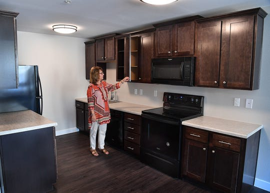 Carol Whitehead, community director for The Landmark on Lamar apartments, talks about the furnishings in one of the unit's kitchens.