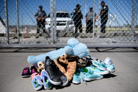 Security personal stand before shoes and toys left at the Tornillo Port of Entry where minors crossing the border without proper papers have been housed after being separated from parents.