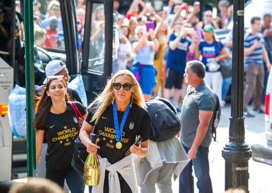 United States women's soccer team members Allie Long, center, and Alex Morgan walk to a hotel Monday, July 8, 2019, in New York.