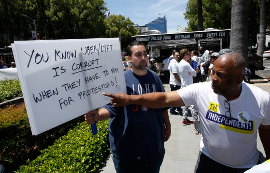 Ride-share driver Pierre Finley, right, a supporter of AB 5, a measure to limit when companies can label workers as independent contractors, questions Ruben Houghtailing, about his opposition to the bill, during a rally in Sacramento, Calif., on July 9.