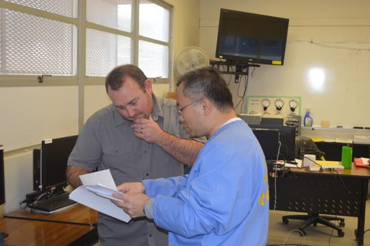 Professor Peter Fulks of Cerro Coso Community College goes over an assignment with one of his students during his Concepts of Criminal Law class at Tehachapi prison.
