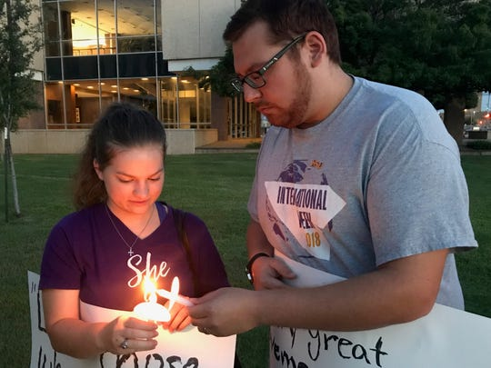 Grace Sosa, left, lights a candle for her husband, Carlo Sosa-Ortiz, at a vigil for those being held at detention centers along the U.S.-Mexico border at Abilene City Hall Friday. The pair were among roughly 80 demonstrators holding signs calling for the centers to be closed.