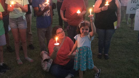 Four-year-old Lena Spaulding holds her candle high during a nationally organized candlelight vigil outside Abilene City Hall Friday. Lena was in attendance with her family, including her mother, Mollie Spaulding, who held her hand during the event.