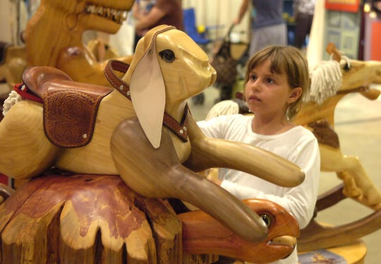 7-year-old Amelia Cruz checks out a rocking bunny by Russ Jacobsohn at the Craft Fair of the Southern Highlands in the Asheville Civic Center in July 2007.  The bi-annual event is in its 60th year.
