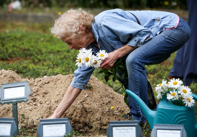 "Alex, who did not give her last name, places flowers on each box of remains of the 14 Kitsap residents buried Saturday. ""We all come to this end, and we're all part of the same planet and energy. I hope they find peace,"" she said."