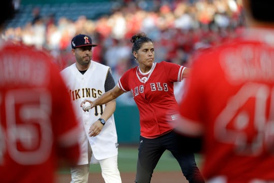 The late Los Angeles Angels pitcher Tyler Skaggs' mother, Debbie Hetman, center in red, throws the game's ceremonial first pitch, at a baseball game between the Angels and the Seattle Mariners on Friday, July 12, 2019, in Anaheim, Calif.