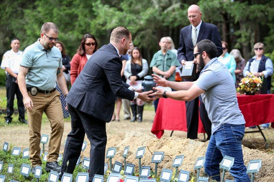 "Kitsap County Coroner Jeff Wallis hands boxes of ashes of the 14 ""indigent"" residents to staff of the Kitsap County Coroner's Office to place in the ground at Silverdale Pioneer Cemetery."