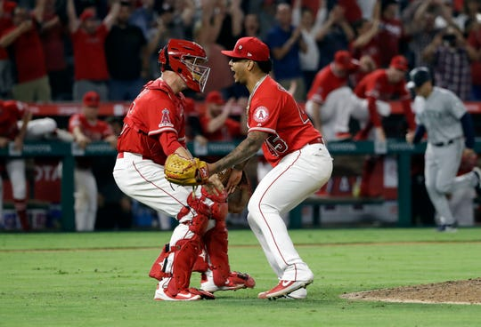 Los Angeles Angels relief pitcher Felix Pena, right, celebrates with catcher Dustin Garneau after the Angels threw a combined no-hitter against the Seattle Mariners during a baseball game Friday, July 12, 2019, in Anaheim, Calif. Taylor Cole pitched the first two innings.