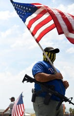 "A man, who identified himself as ""Good Citizen,"" holds an American flag and gun during the Close the Camps counter protest, Saturday, July 13, 2019, at Cole Park. The man and four others were a small counter group that brought American flags, Trump flags and guns to the counter protest across the street from the Close the Camps rally."