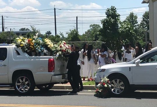 Floral displays are carried out of New Life Ministries after funeral services Saturday for Curtis Jenkins III of Camden.