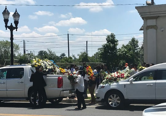 Workers carry floral displays from Saturday's funeral services for Curtis Jenkins III of Camden.