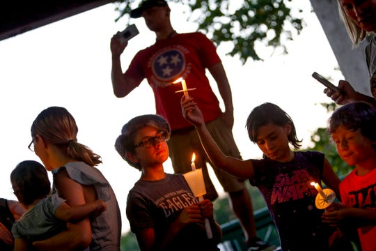 Josilea Garlow, 12, left, and Aayla Garlow, 8, right, hold up candles in a demonstration during the Lights for Liberty vigil, an event organized across the country to protest conditions at immigration detention centers, with Clarksville Indivisible helping organize the local one at McGregor Park in Clarksville, Tenn., on Friday, July 12, 2019.