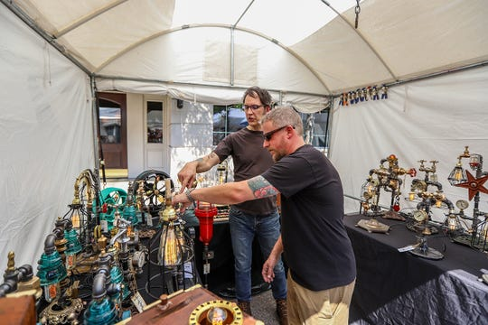 Joseph Mazzola, 65, of Detroit shows Justin Foust, 35,of Livonia his repurposed mid-century, functional scluptures he makes during Art In The Park event in Plymouth, Mich. photographed on Saturday, July 13, 2019. Mazzola's company is called Eastworks Detroit.