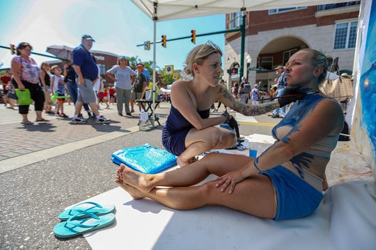 Kristen Zipp, 36, of Portland, Oregon paints a live mural with the help of model Emily Harris, 39, of Canton, during Art In The Park event in Plymouth, Mich. photographed on Saturday, July 13, 2019. Zipp is representing D&M Art Studio in Canton, Mich. and has been doing this demonstration for 10 years.