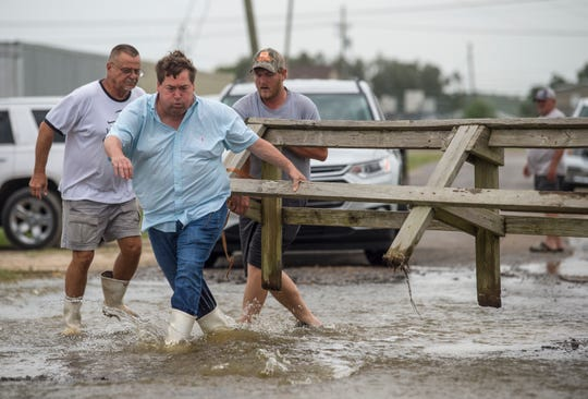 Louisiana Lt. Gov. Billy Nungesser, left center, helps move a wooden barricade to block a road where water was rising in Plaquemines Parish just south of New Orleans as Hurricane Barry makes landfall along the coast on Saturday, July 13, 2019.