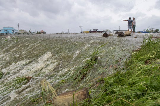 Chris Nguyen and his father, Trung, look at the moving water that breached the top of a levee in Plaquemines Parish just south of New Orleans as Hurricane Barry makes landfall along the coast on Saturday, July 13, 2019.