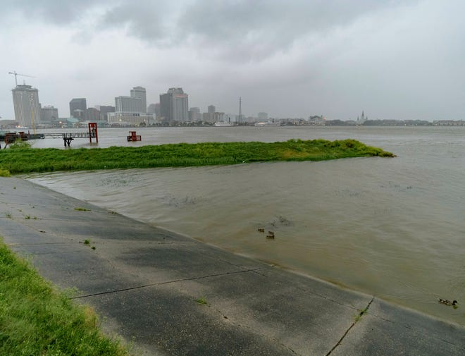 As rain bands cover the French Quarter, a green strip remnant of an old Mississippi River levee is nearly submerged as seen atop the current concrete covered Mississippi River levee in Algiers Point where the unusually high river is at 16.9 feet, which is just under the minor flood stage of 17 feet, in New Orleans, Friday, July 12, 2019, ahead of landfall of Tropical Storm Barry. The levees protect to at least 20 feet.