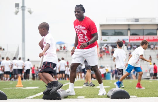 Immokalee High School graduate and NFL player D'Ernest Johnson, center, leads drills on Saturday at the Rising Stars football camp at Immokalee High School. Johnson joined fellow graduates and NFL players Mackensie Alexander, Deadrin Senat and J.C. Jackson in leading the camp — which was presented by the Tommy Bohanon Foundation.